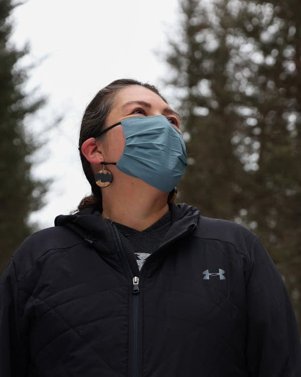 A person wearing a face mask stands outside near pine trees.