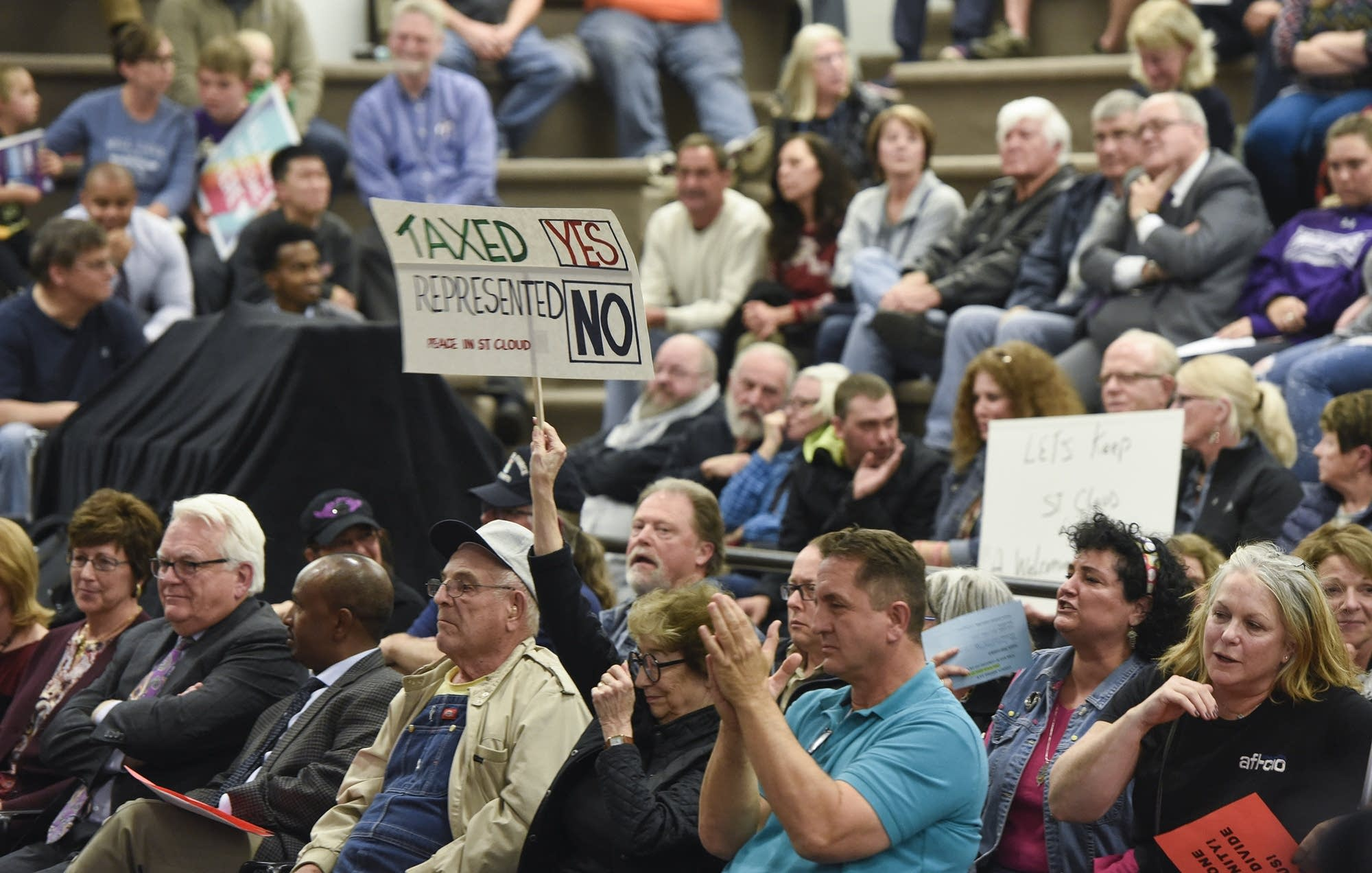 People hold signs during a St. Cloud City Council discussion on refugees.