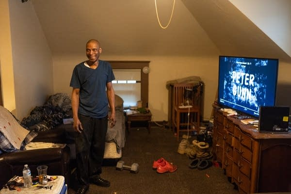 Craig Spivey stands in his studio apartment inside of a rooming house