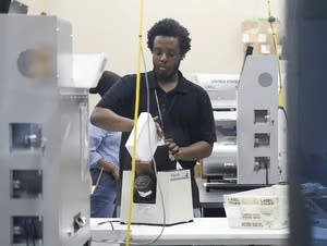 Workers load ballots into machines.