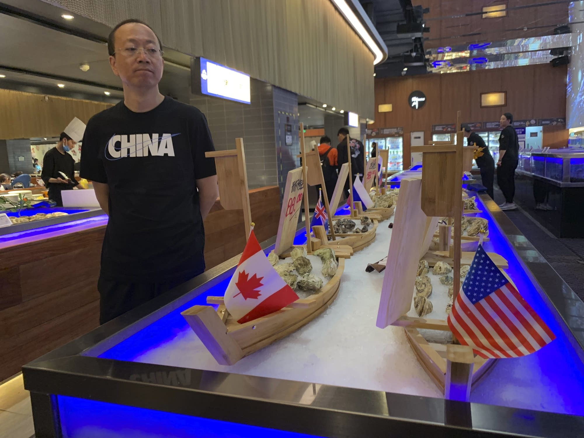 A shopper eyes display of seafood including oysters from the U.S.