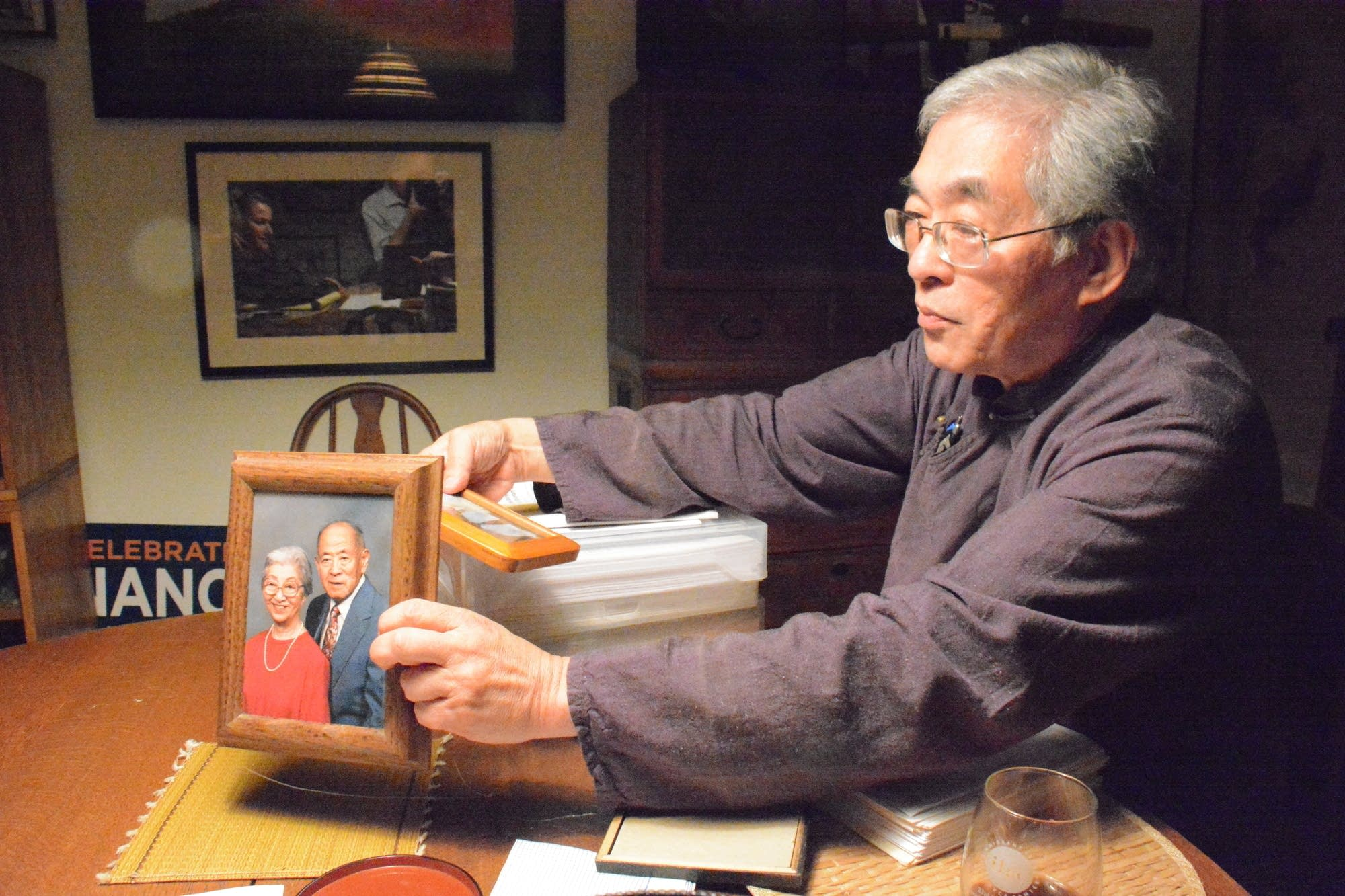 Norm Ishimoto holds up a photo of his parents, Paul and May Ishimoto.