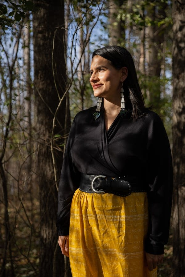 A woman in a black shirt and yellow skirt stands in a forest.
