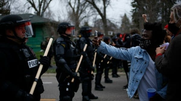 Protesters confront police near the scene of a fatal police shooting