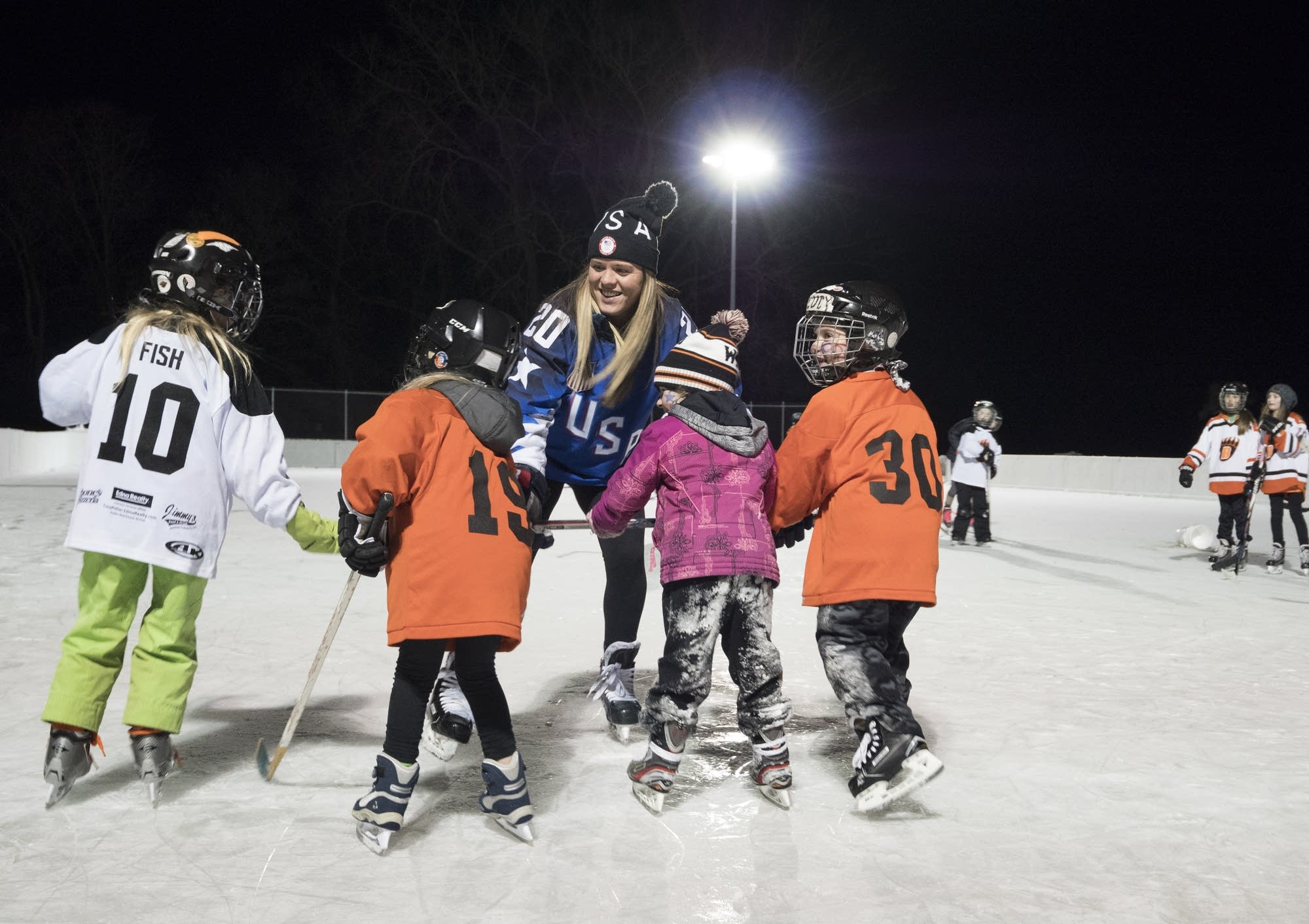 Olympic gold medal hockey player Hannah Brandt skates with youth.