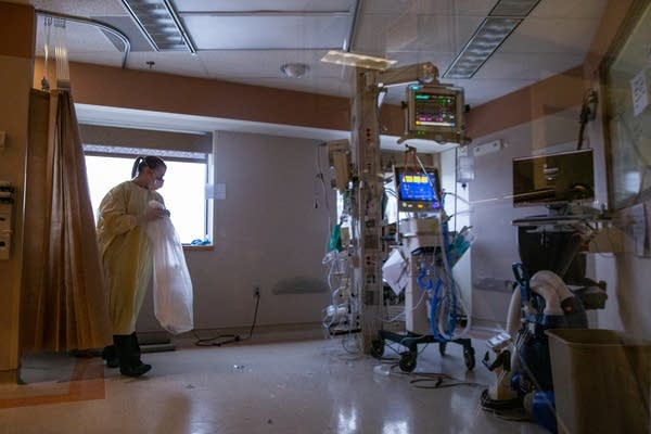A woman wears PPE while cleaning a hospital room.
