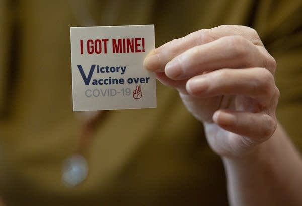 "A sticker reads ""I got mine. Victory vaccine over COVID-19"""