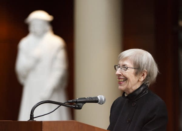 A smiling woman stands at a podium.