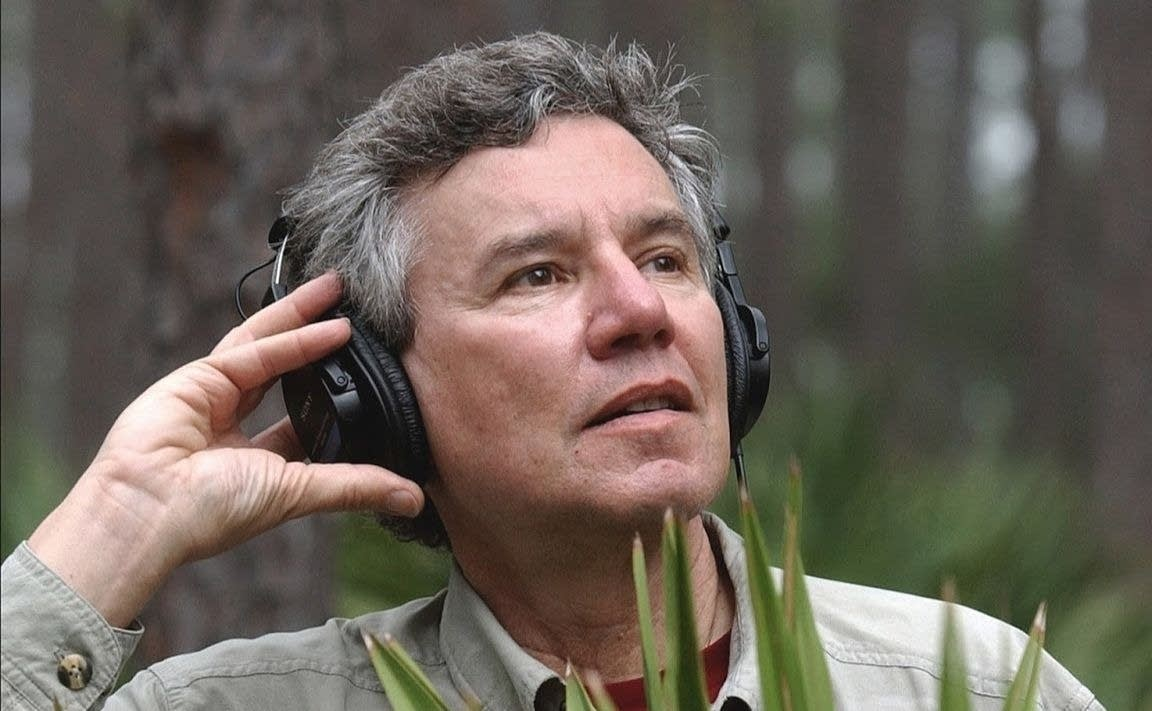 A man with headphones listens to nature.