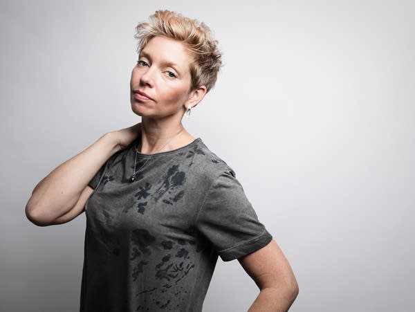 A woman with short blonde hair in a grey t-shirt.