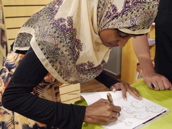 Zaynab Abdi, from Yemen, autographs a book.