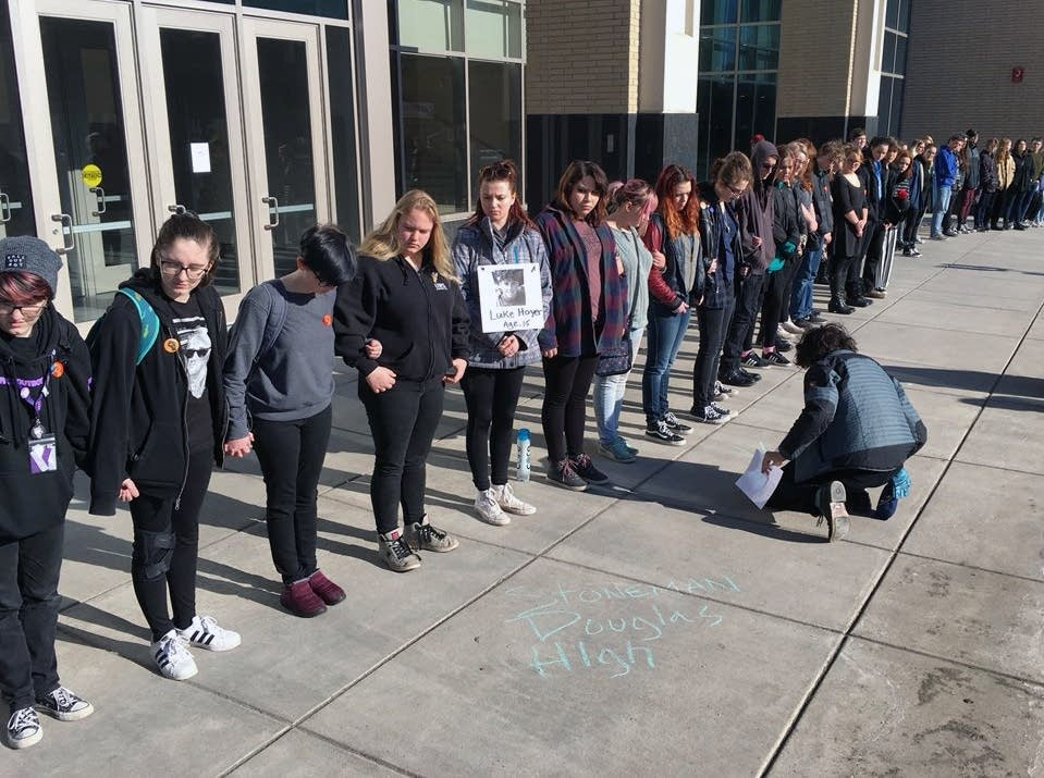 Students write names of the Parkland, Fla, school shooting victims.