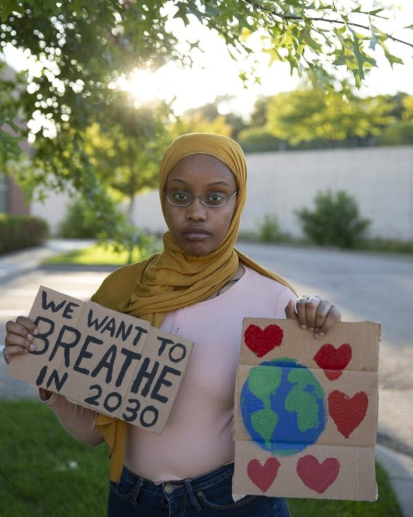 A teenage girl holds  two handmade cardboard signs