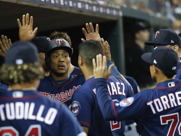 Baseball players high-five each other.