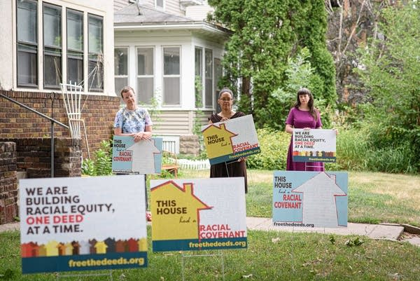 Three people stand with various lawn signs.