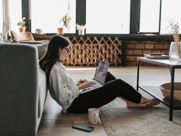 A woman works in a spacious home with a laptop.
