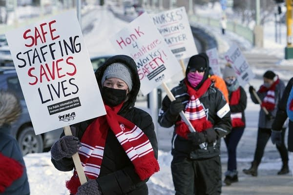 People in masks and scarves carry signs during a demonstration.