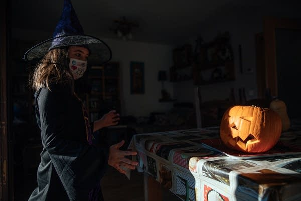 A person dressed in a witch costume near a pumpkin.