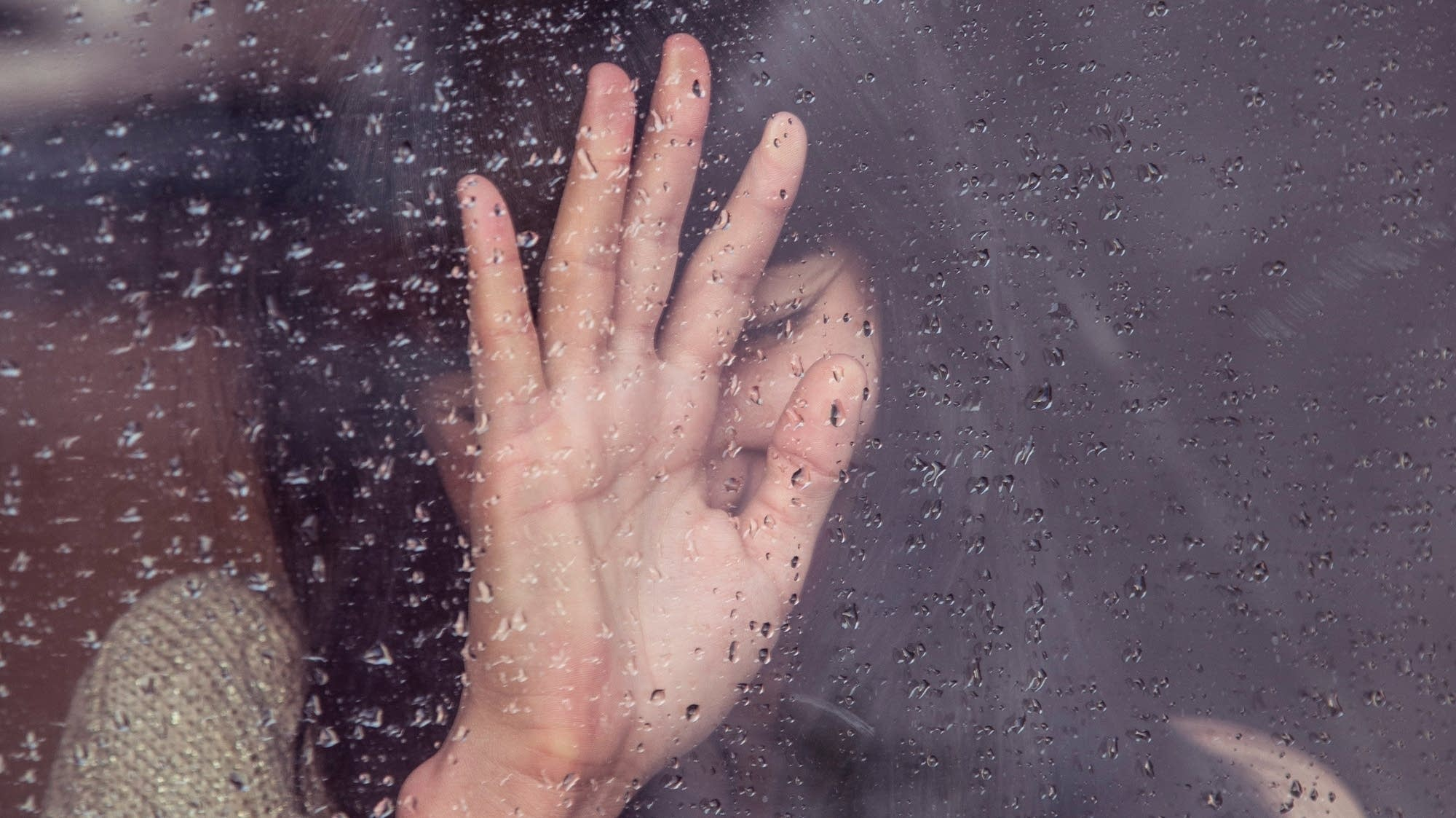 A sad woman presses her hand against a rainy window.