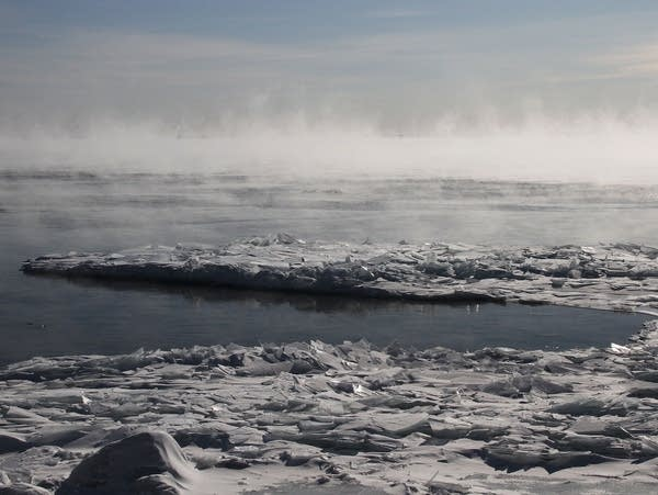 Sea smoke rises from a patch of open water on icy Lake Superior