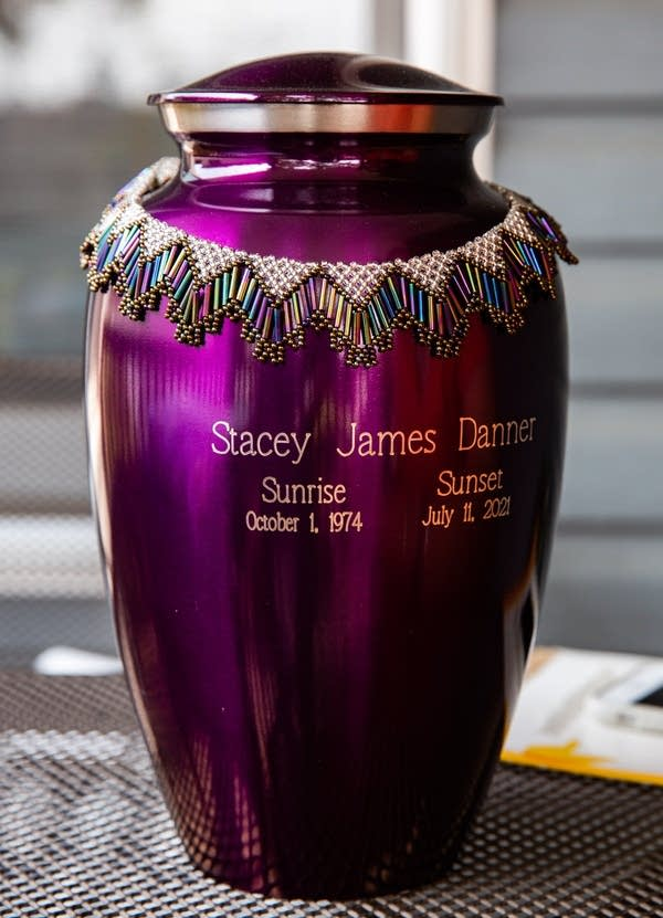 A purple urn sits on a table.