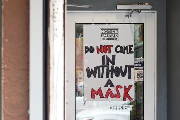 A sign on the entrance to AA Market reads: Do not come in without a mask.