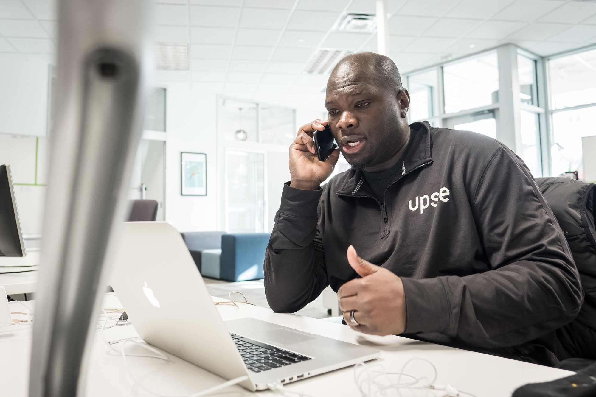 Clarence Bethea, CEO of Upsie, speaks on the phone at the Upsie office.