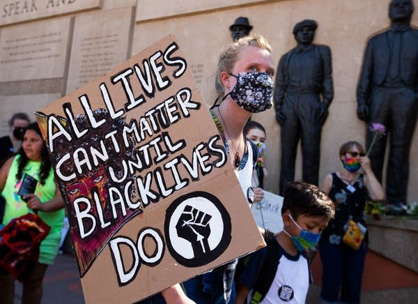 "Person holds a sign saying ""All lives can't matter until black lives do"""