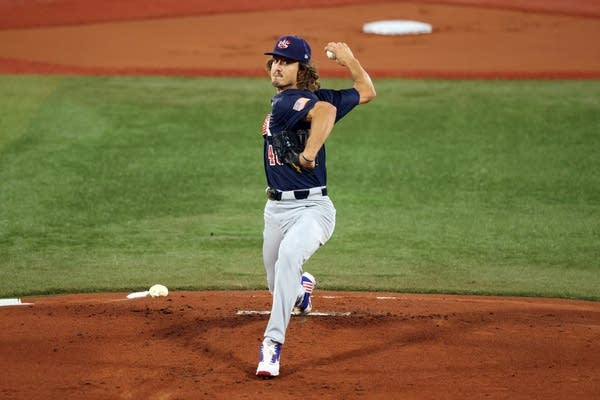 A baseball player winds up for a pitch.