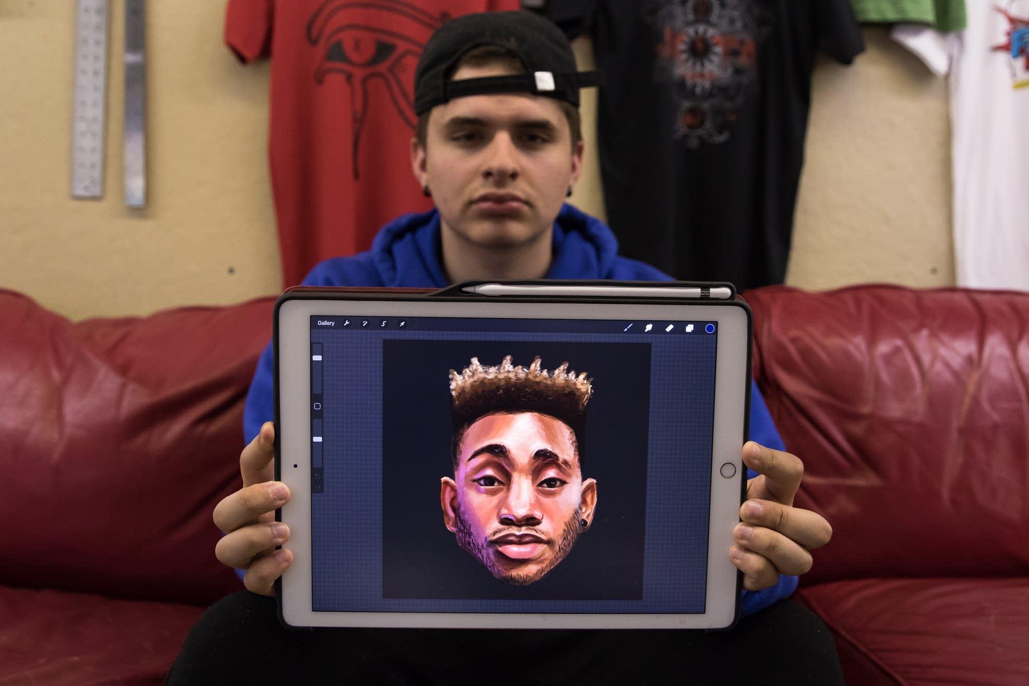 Senior designer Patricio Delara, 19, poses with a portrait.