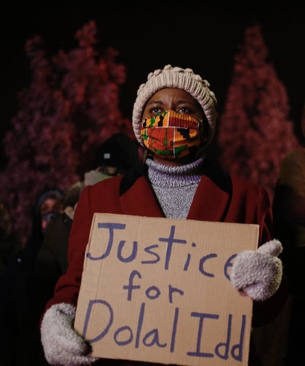 A person holding a sign that reads justice for Dolal Idd.