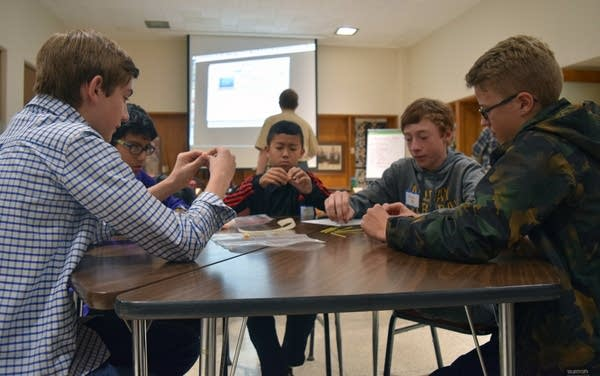 Boys build towers out of uncooked spaghetti and marshmallows.