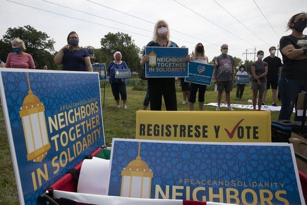"""A group holding signs that read """"neighbors together in solidarity."""""""