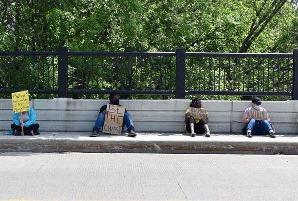People sit on the side of a road with signs.