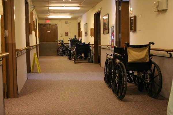 Wheelchairs sit in a hallway at a care facility