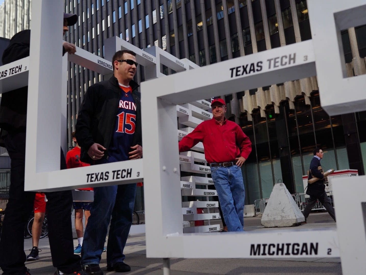A Texas Tech fan waits to take a photo with a March Madness bracket.