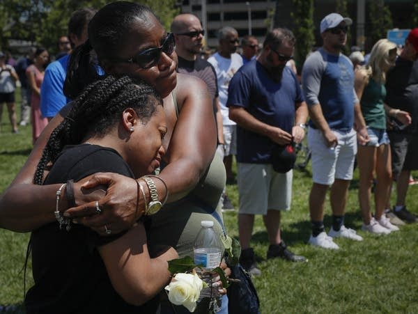 Mourners gather at a vigil following a nearby mass shooting