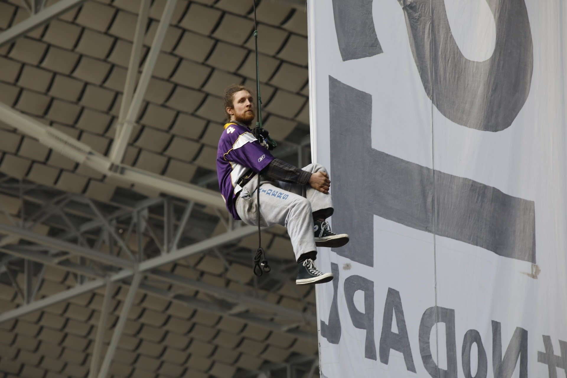 A protester hangs from the grid of US Bank Stadium