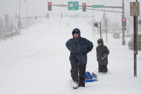 Paul Osterman pulls one son in a sled behind him while another follows.
