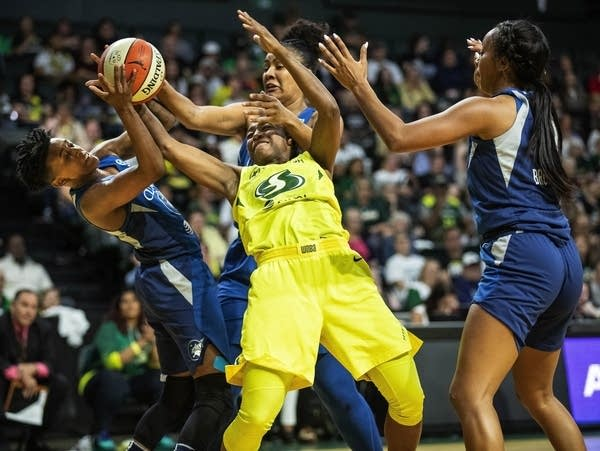 Three Lynx players surround a Storm player with the ball.