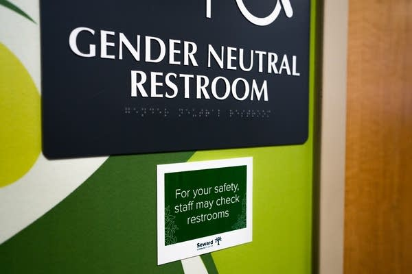 """A small green signs hangs under a """"Gender Neutral Bathroom"""" sign."""