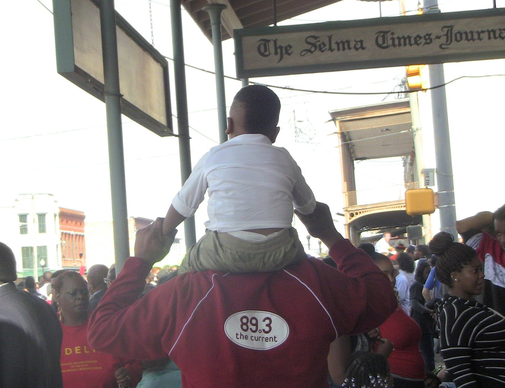 Derrick Stevens carries his grandson through Selma