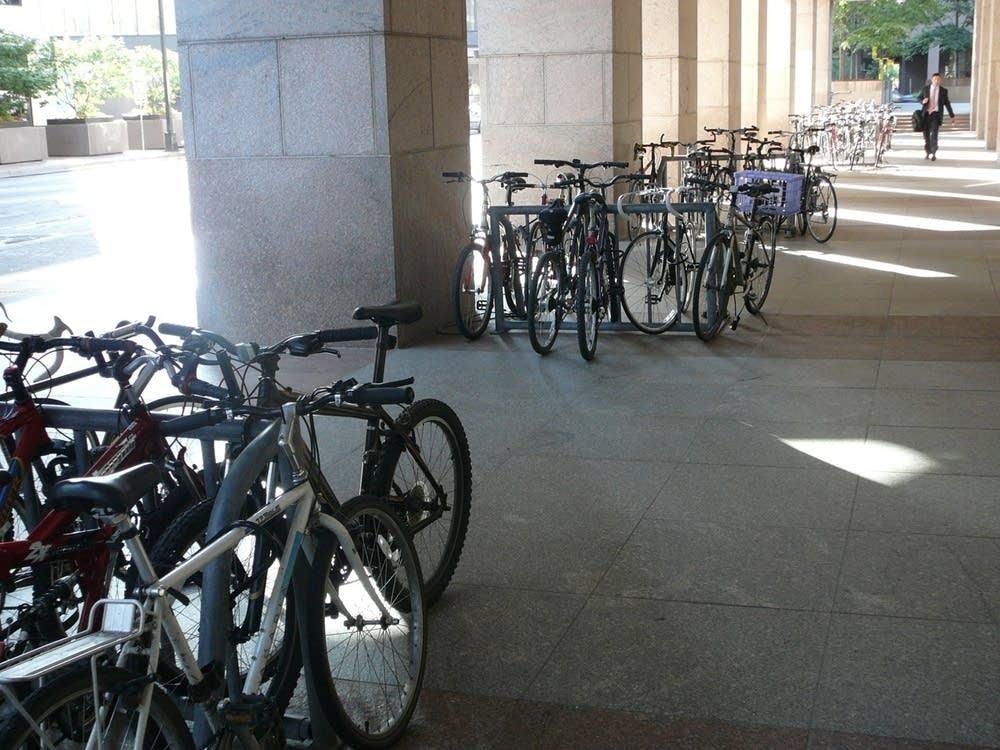 Bike commuters use a crowded bike rack.