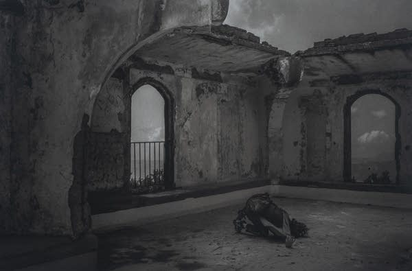 A black and white photograph of a person in a worn down building.