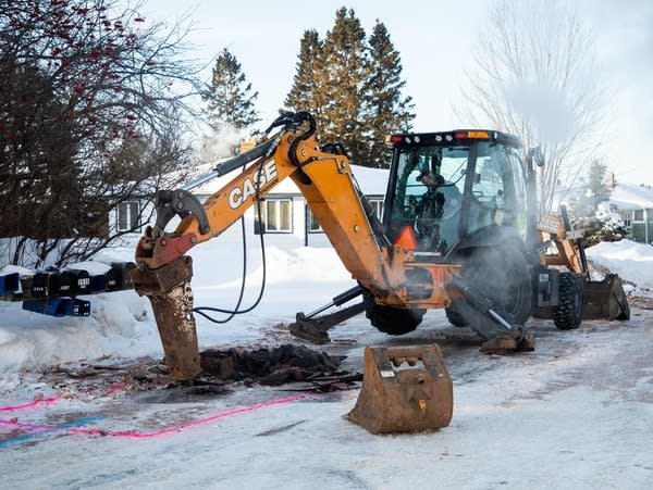City of Duluth workers dig into Harvey Street after a water pipe burst.