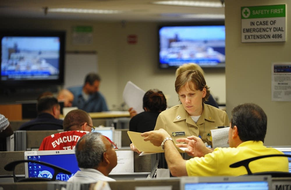 Workers look over documents in the FEMA