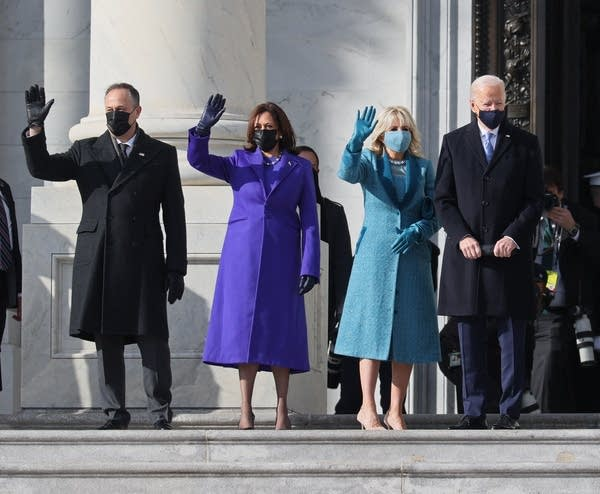 Four people in masks wave.