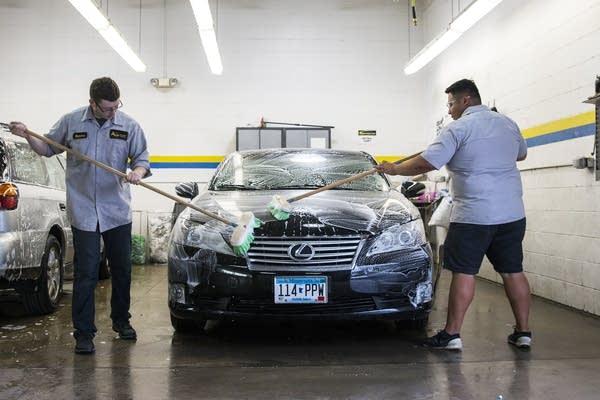 Abra Employees wash a Lexus.