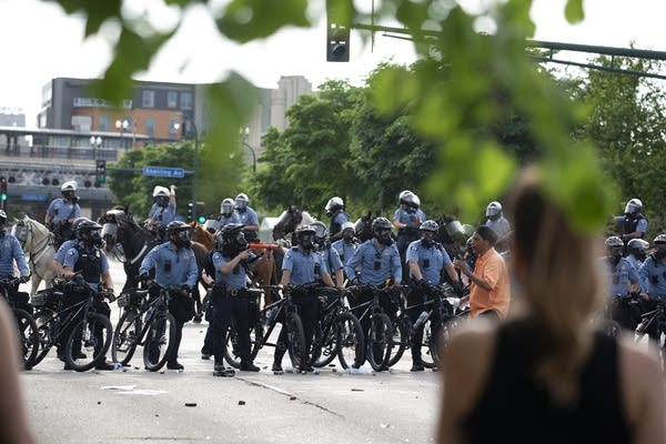 A line of police officers in riot gear with bicycles
