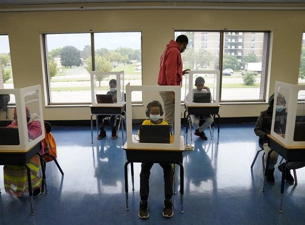 Children sit behind plastic barriers at desks spaced apart in a classroom.